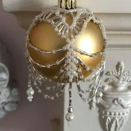 Ivory and silver swags and tails bauble cover on a matt gold ball ornament.