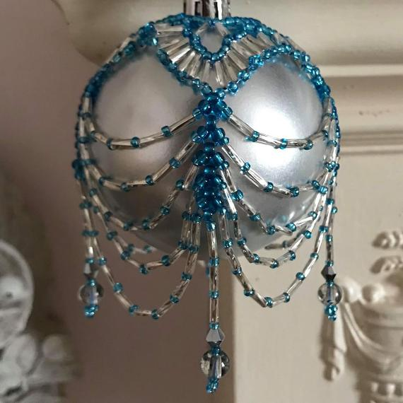 Swags and Tails beaded bauble in turquoise and silver beads on a matt silver glass ball ornament.