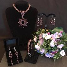 Purple pendant necklace, bracelet and three pairs of earrings shown with some beautiful purple flowers.