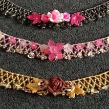 Three netted necklaces in pink, grey and gold beads with golden rutilated quartz semi-precious stones and decorated with various lucite flowers and polymer clay roses.