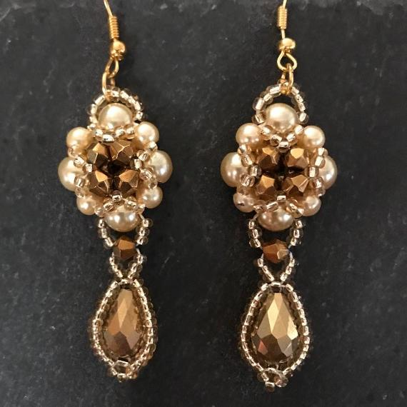Hulton Abbey earrings made from two sizes of gold pearls with gold metallic crystals.