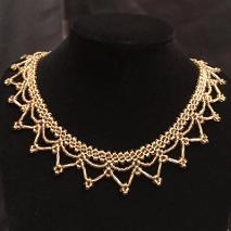 Gold lace handmade necklace on a black velvet stand.