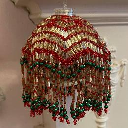 Lumiere bauble made from red seed beads and gold bugle bads with green pearls on a silver Christmas tree bauble.