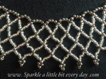 Netted necklace made with silver and grey seed beads.