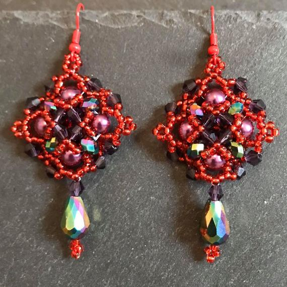 Persephone earrings made in shades of red and blue so they look like a pomegranate.