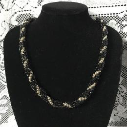 Black and silver spiral rope necklace on a black velvet bust with a white lace background.