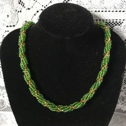 Green seed bead spiral rope necklace on a black velvet display bust in front of a white lace background.