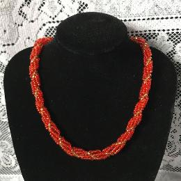 Red spiral rope necklace on a blacj velvet bust in front of a white lace cloth.
