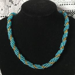 Turquoise and green spiral rope necklace on a black velvet dispaly bust in front of a white lace cloth.