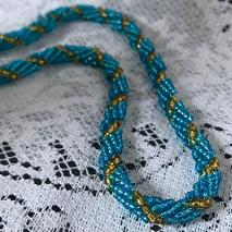 Turquoise and green spiral rope necklace on a white lace tablecloth.