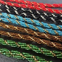 Spiral ropes in five different colours lying diagonally in double rows on a grey slate.